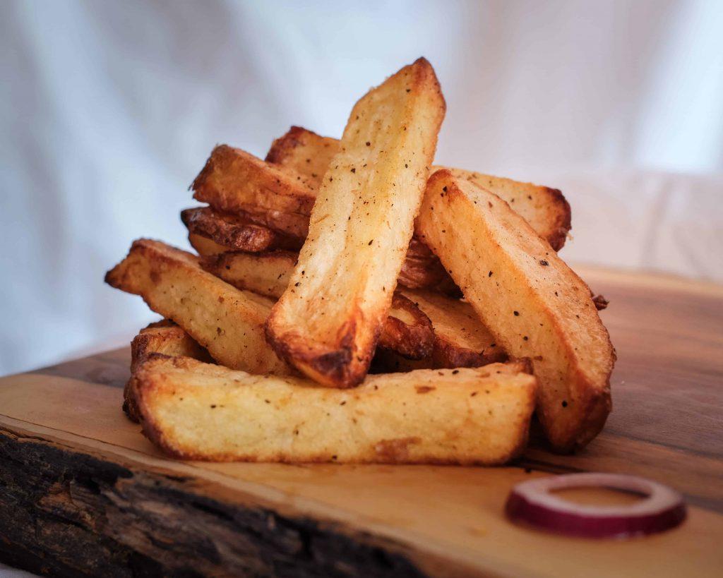 Airfryer potato fries on wooden board.