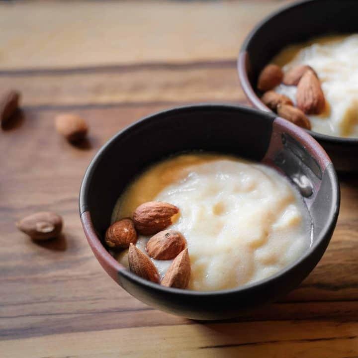 Vegan Chickpea Yogurt in black bowl with almonds.