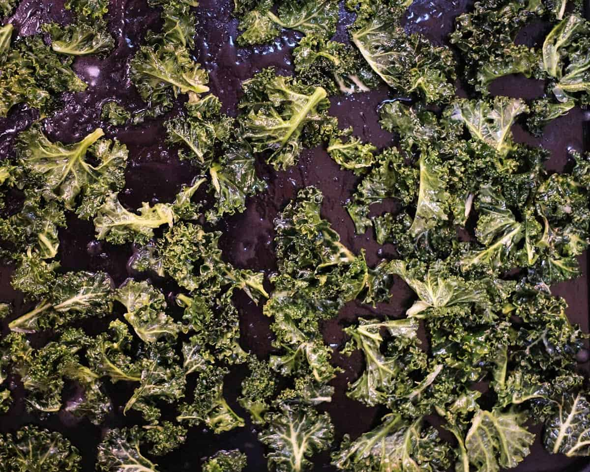 Kale rubbed in lemon juice and oil on a black tray.