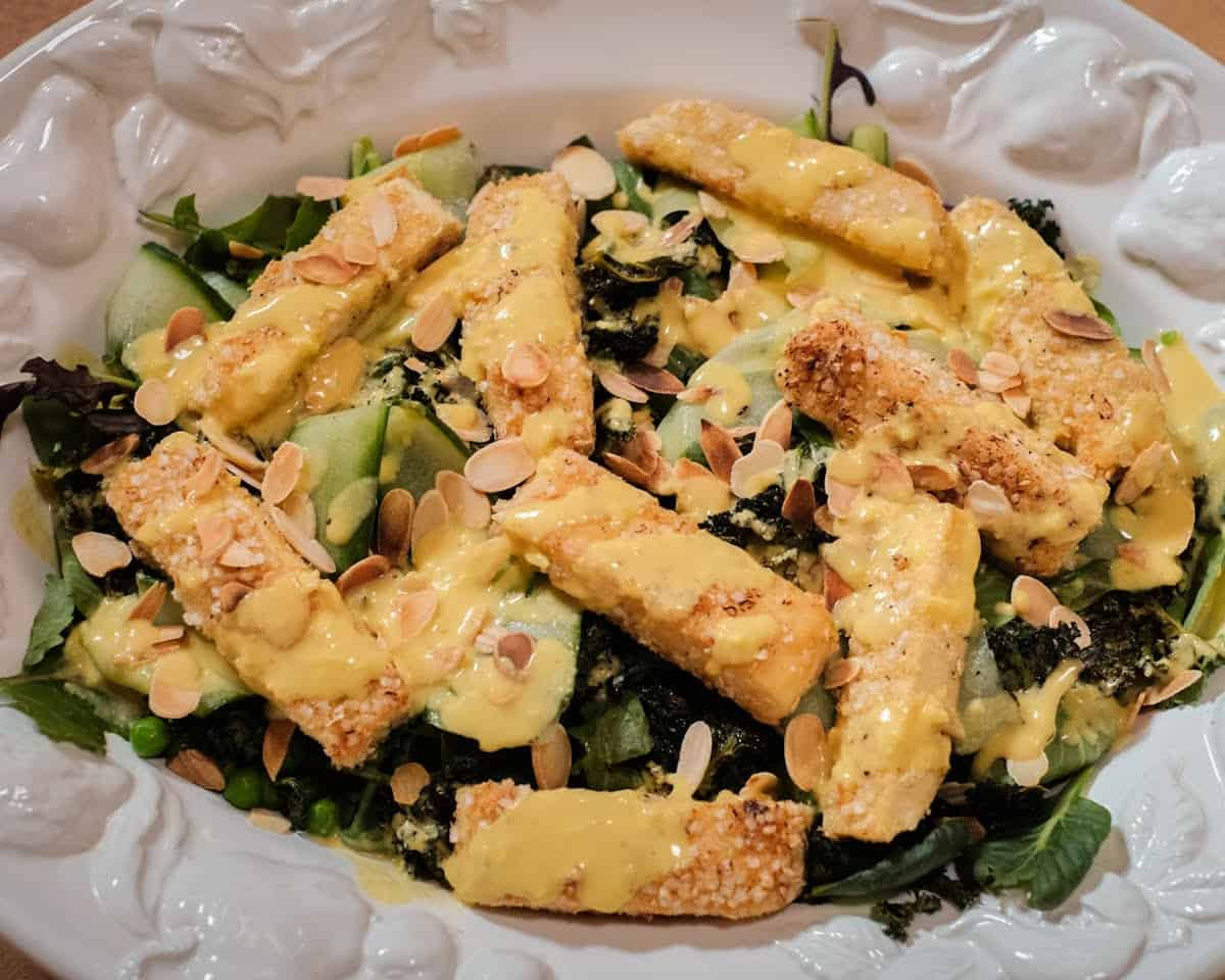 Caesar Salad with crispy tofu and homemade creamy and tangy salad dressing in a white bowl.