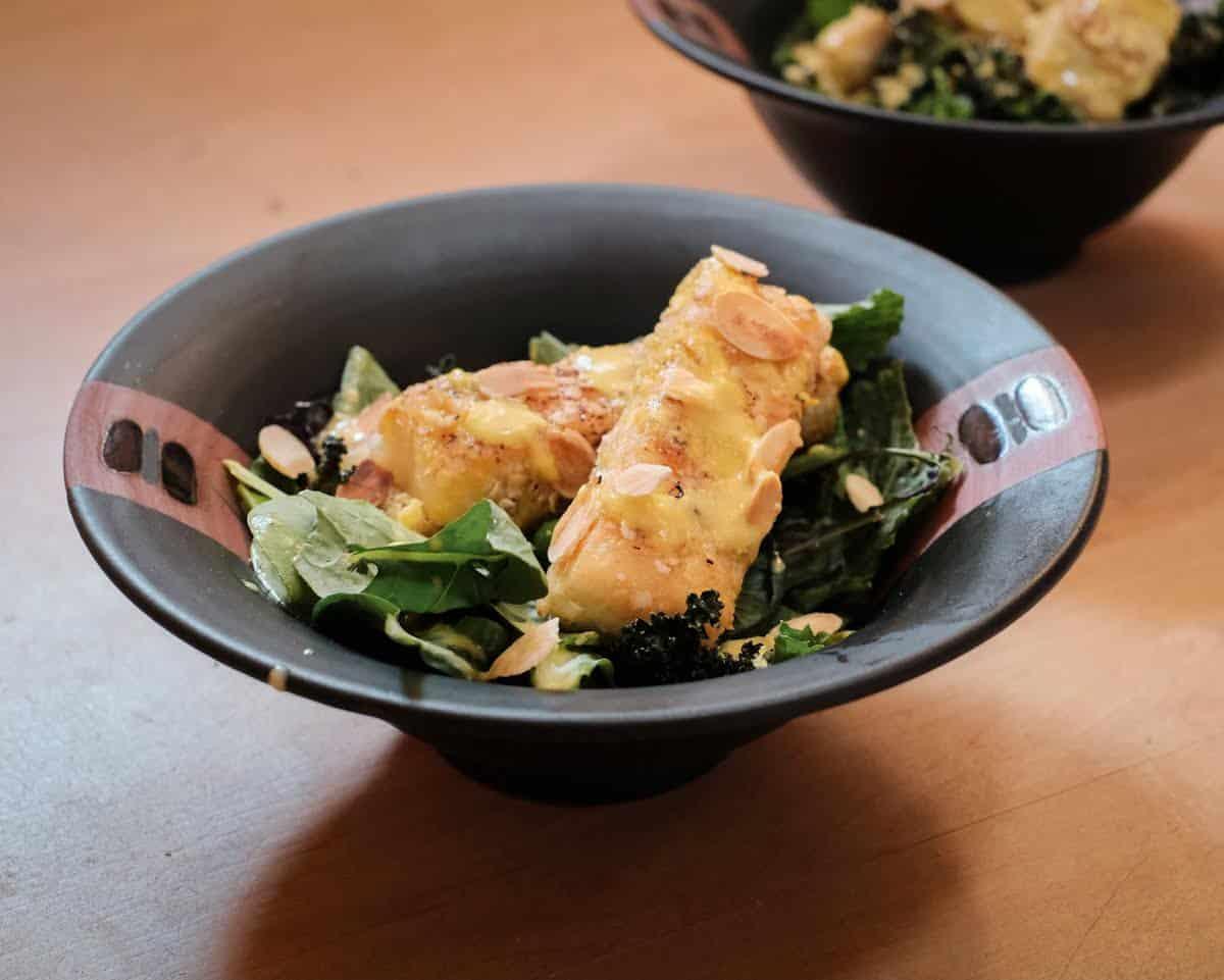Vegan Caesar Salad with tofu, in a black bowl.