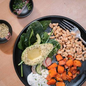 Roasted Vegetable Harvest Bowl with Pumpkin, Avocado and crispy beans next to a pickled salad on a black plate.