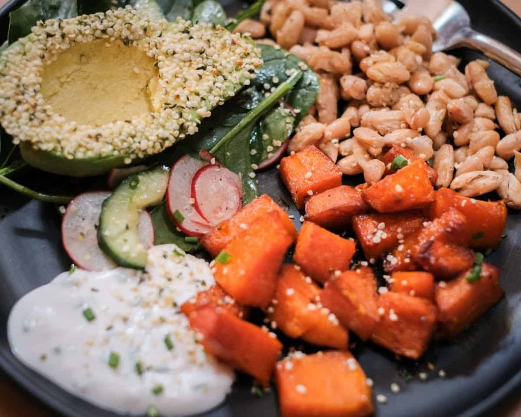 Roasted Vegetable Harvest Bowl close up image featuring hemp covered avocado, maple roasted pumpkin, crispy beans and a vegan ranch dressing on a black plate.